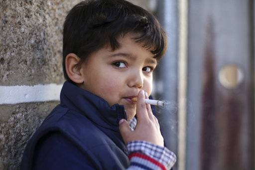 Fernando, 6-years-old, smokes a cigarette in the village of Vale de Salgueiro, northern Portugal, during the local Kings' Feast Saturday, Jan. 6, 2018. The village's Epiphany celebrations, called Kings' Feast, feature a tradition that each year causes an outcry among outsiders: parents encourage their children, some as young as 5, to smoke cigarettes. Parents buy the packs of cigarettes for their children. Locals say the practice is centuries-old, but nobody is sure what it symbolizes nor why the children are incited to smoke. (AP Photo/Armando Franca)