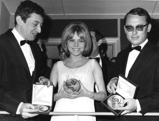 "FILE - In this March 20, 1965 file photo, Winner, 18-year-old French singer France Gall, singing for Luxembourg in the Eurovision Song Contest, poses with her award with Serge Gainsbourg, left, and orchestra director Alain Gorauguer, right, in Naples. Gall, who collected hits and sold millions of albums over a four-decade career, has died. She was 70. Her agent Genevieve Salama told The Associated Press that the singer, with her signature blond bangs, died of cancer in the Paris region on Sunday, Jan. 7, 2018. French President Emmanuel Macron wrote in a tweet that Gall ""lasted through time thanks to her sincerity and generosity�, leaving ""songs known to all French.� (AP Photo/Guilio Broglio, File)"