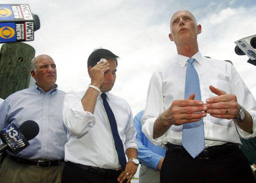 FILE - In this Aug. 13, 2013, file photo, Rep. Steve Southerland, R-Fla. and Sen. Marco Rubio listen to Florida Gov. Rick Scott announce a lawsuit against the state of Georgia, while touring Apalachicola, Fla. Florida is hoping the Supreme Court will come to the rescue of this slice of northwestern Florida, which the state says has been devastated by greedy water users in Georgia. The high court hears argument Monday, Jan. 8, 2018, in the long-running water war between the neighboring states. (AP Photo/Phil Sears, File)