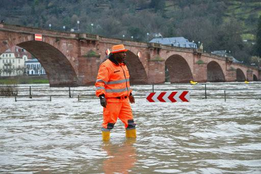 In this Jan. 6, 2018 photo, a staff member of a street cleaning company wades through the water on a flooded quayside road along the river Neckar in Heidelberg, Germany. (Uwe Anspach/dpa via AP)