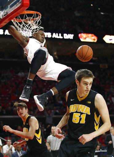 Maryland forward Bruno Fernando, top, of Angola, dunks on Iowa forwards Nicholas Baer (51) and Luka Garza in the second half of an NCAA college basketball game in College Park, Md., Sunday, Jan. 7, 2018. Fernando contributed a team-high 21 points to Maryland's 91-73 win. (AP Photo/Patrick Semansky)