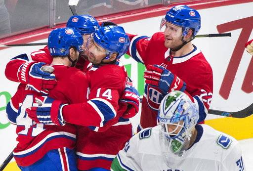 Montreal Canadiens' Paul Byron (41) celebrates with teammates Tomas Plekanec (14) Brendan Gallagher (11) and Karl Alzner (22) after scoring against Vancouver Canucks goaltender Anders Nilsson during the third period of an NHL hockey game in Montreal, Sunday, Jan. 7, 2018. (Graham Hughes/The Canadian Press via AP)