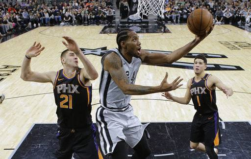 San Antonio Spurs forward Kawhi Leonard (2) scores as Phoenix Suns center Alex Len (21) and guard Devin Booker (1) defend during the first half of an NBA basketball game Friday, Jan. 5, 2018, in San Antonio. San Antonio won 103-89. (AP Photo/Eric Gay)