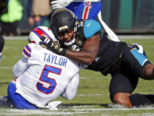 Jacksonville Jaguars defensive end Yannick Ngakoue, right, draws a penalty by hitting Buffalo Bills quarterback Tyrod Taylor (5) with helmet-to-helmet contact in the first half of an NFL wild-card playoff football game, Sunday, Jan. 7, 2018, in Jacksonville, Fla. (AP Photo/Stephen B. Morton)