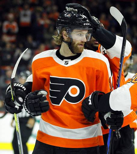 Philadelphia Flyers' Sean Couturier gets a pat on the helmet from teammate Wayne Simmonds after scoring a goal during the second period of an NHL hockey game against the Buffalo Sabres, Sunday, Jan. 7, 2018, in Philadelphia. (AP Photo/Tom Mihalek)