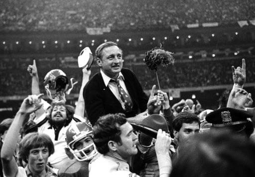 FILE - In this Jan. 1, 1981, file photo, Georgia football coach Vince Dooley is carried off the field after Georgia defeated Notre Dame in the Sugar Bowl. Long before Dooley was lifted to the shoulders of his players after coaching the Herschel Walker-led Georgia Bulldogs to the 1980 national championship, he had his first postgame ride after beating Bear Bryant and Alabama in 1965. Georgia's showdown with Alabama for the national title on Monday, Jan. 8, 2018, night has rekindled Dooley's memories of both big wins. (AP Photo/Gene Blythe, File)