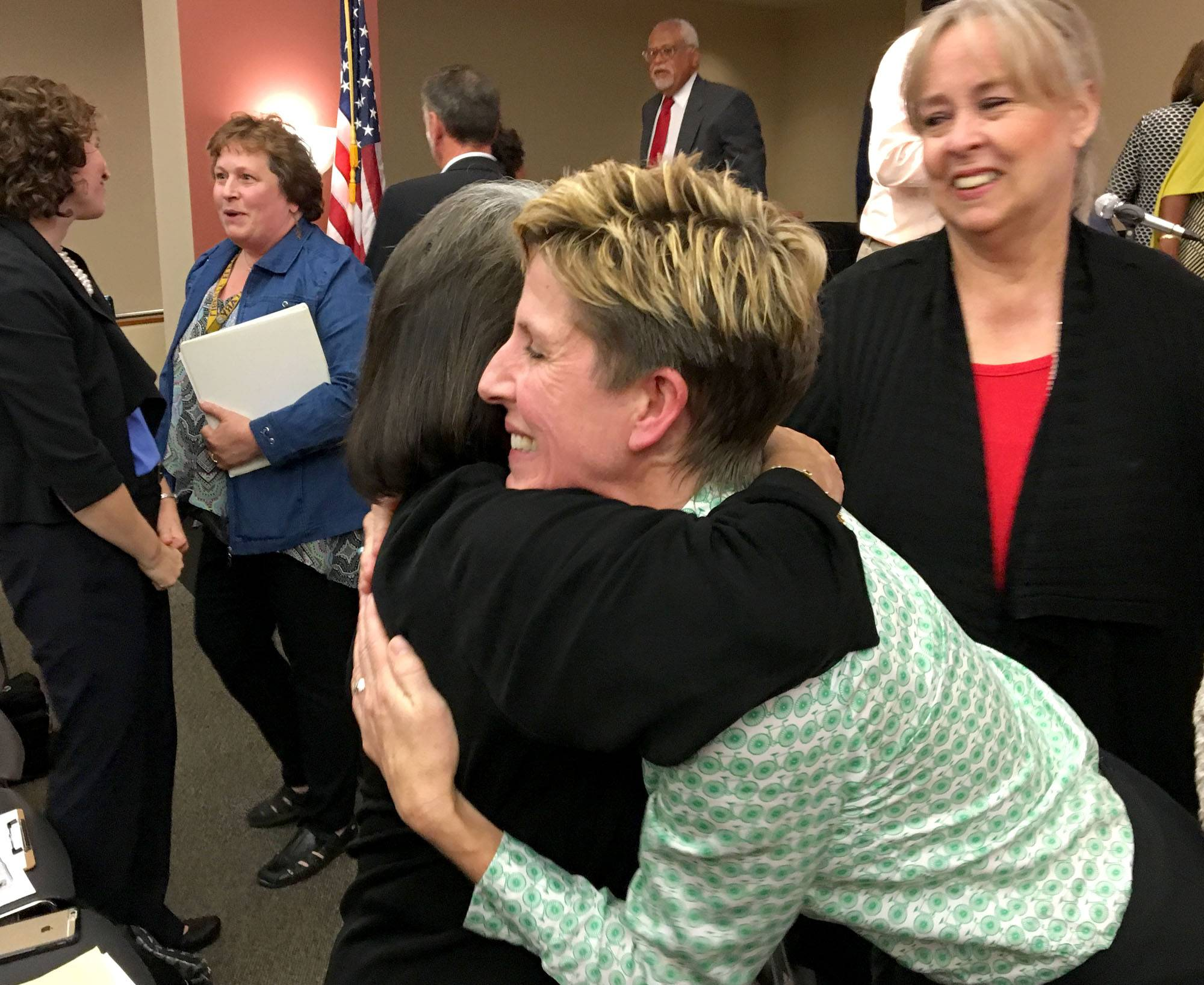 Kerin Kelly, president of the Elgin Charter School Initiative, gets hugs after the group won state approval for a new charter school in Elgin in October.