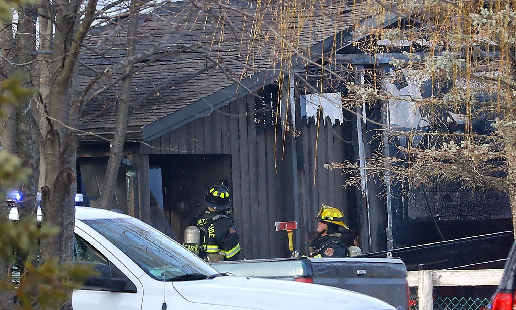 Firefighters investigate a blaze that destroyed a barn near Libertyville on Tuesday.