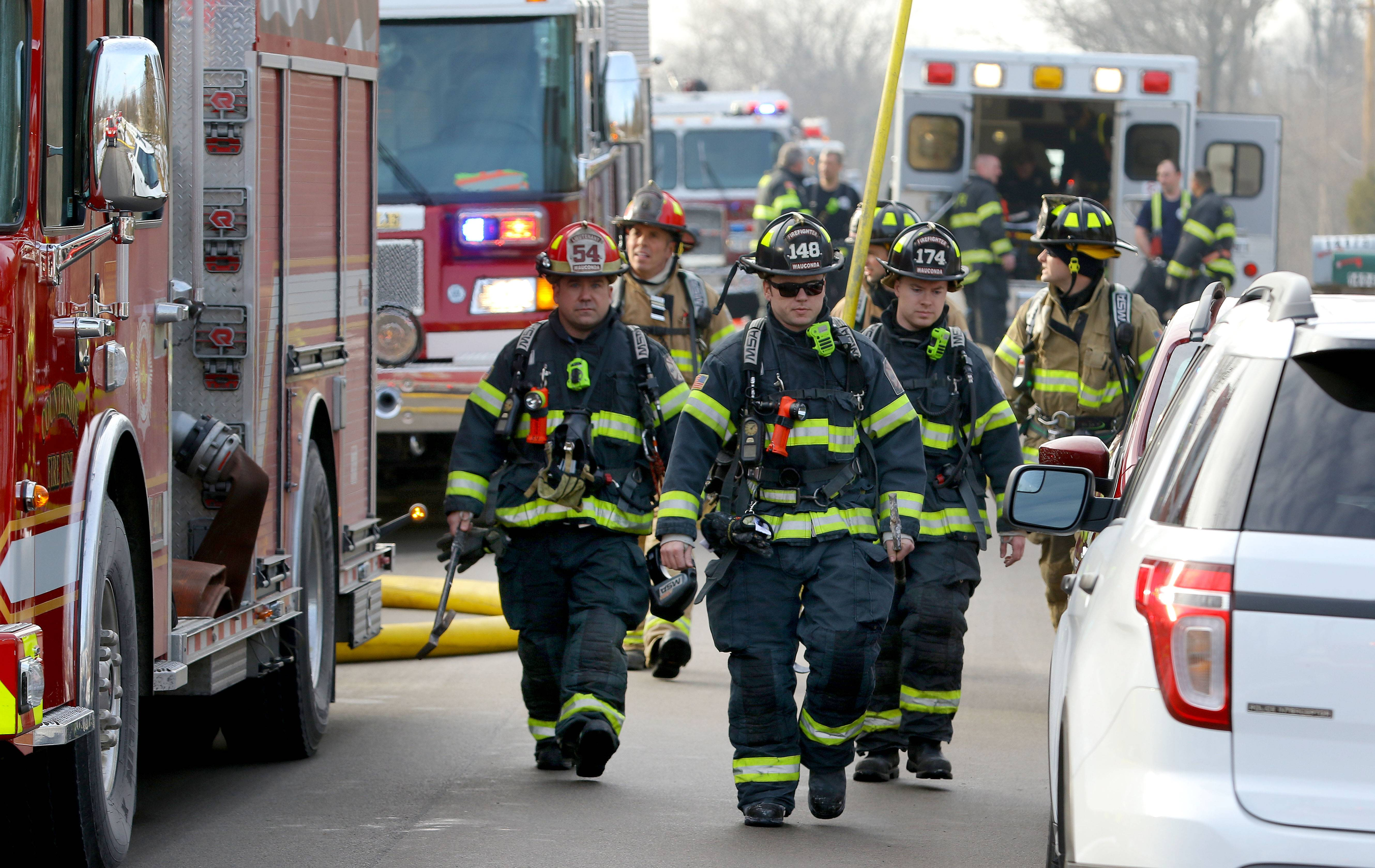 Firefighters head to the scene of a blaze that destroyed a barn near Libertyville on Tuesday.