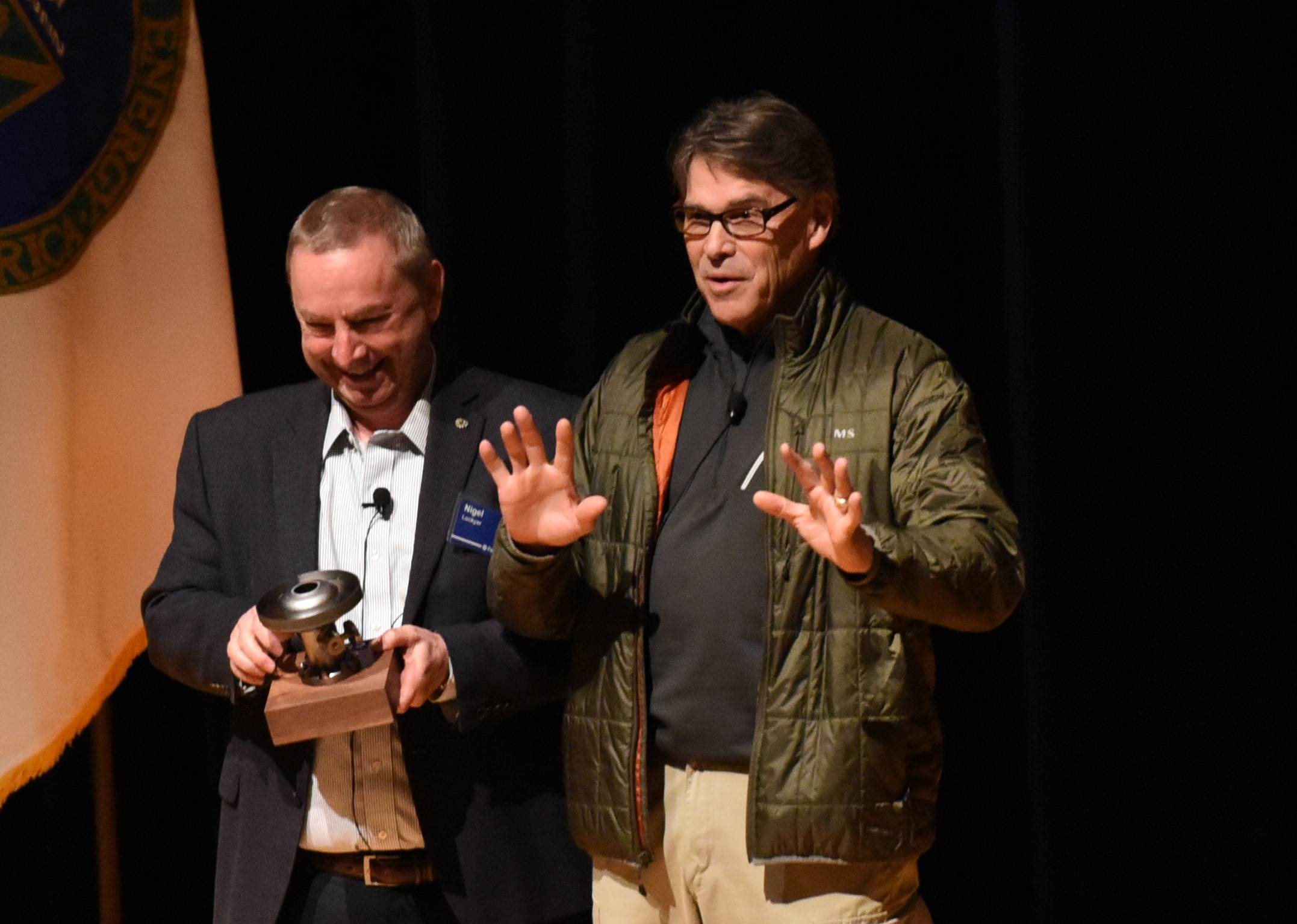 Secretary of Energy Rick Perry receives a gift from director Nigel Lockyer after a speech Tuesday at Fermilab in Batavia.