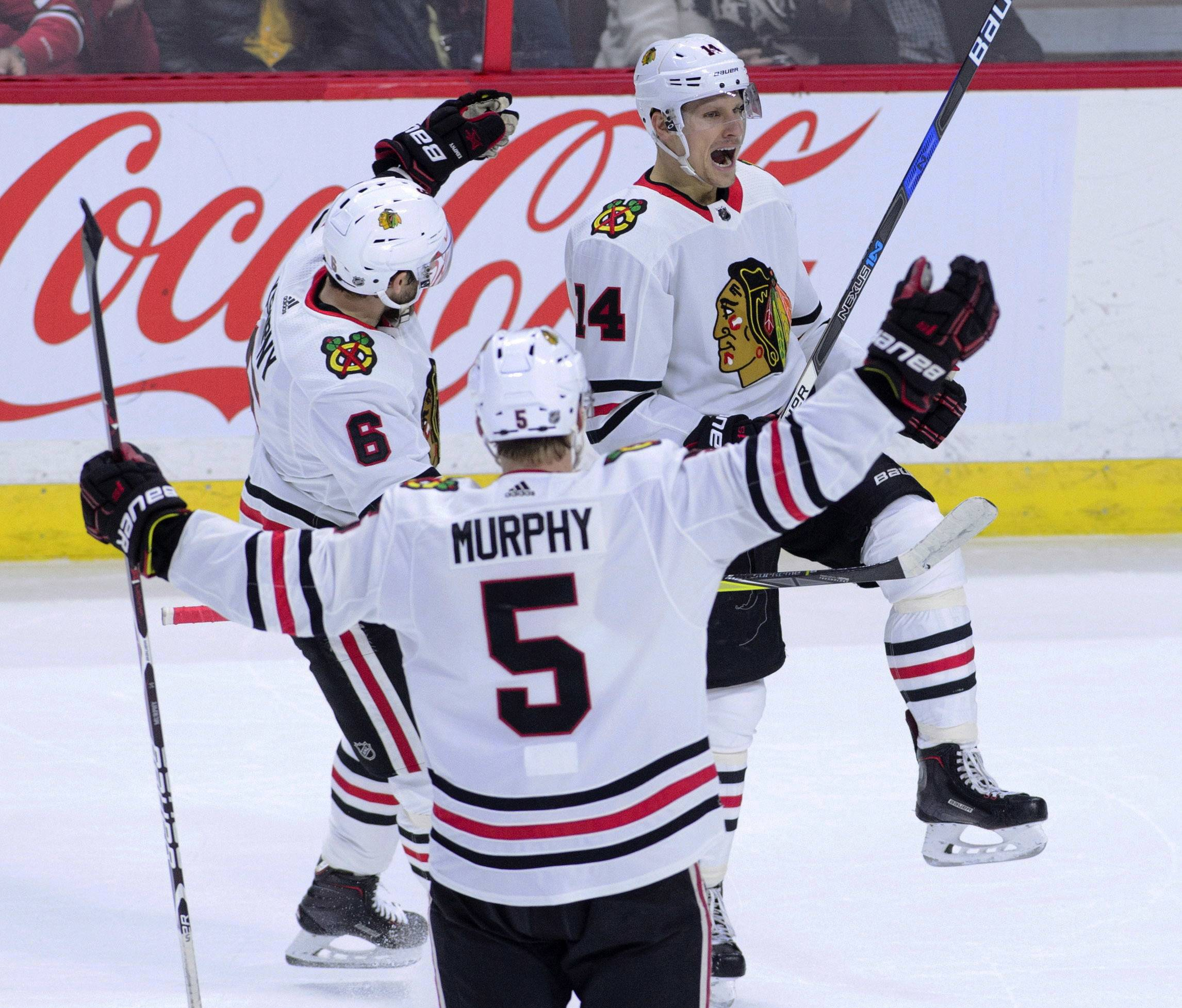 Chicago Blackhawks' Richard Panik (14) celebrates a goal with teammates Michal Kempny (6) and Connor Murphy (5) during the first period of an NHL hockey game, Tuesday, Jan. 9, 2018, in Ottawa, Ontario. (Sean Kilpatrick/The Canadian Press via AP)