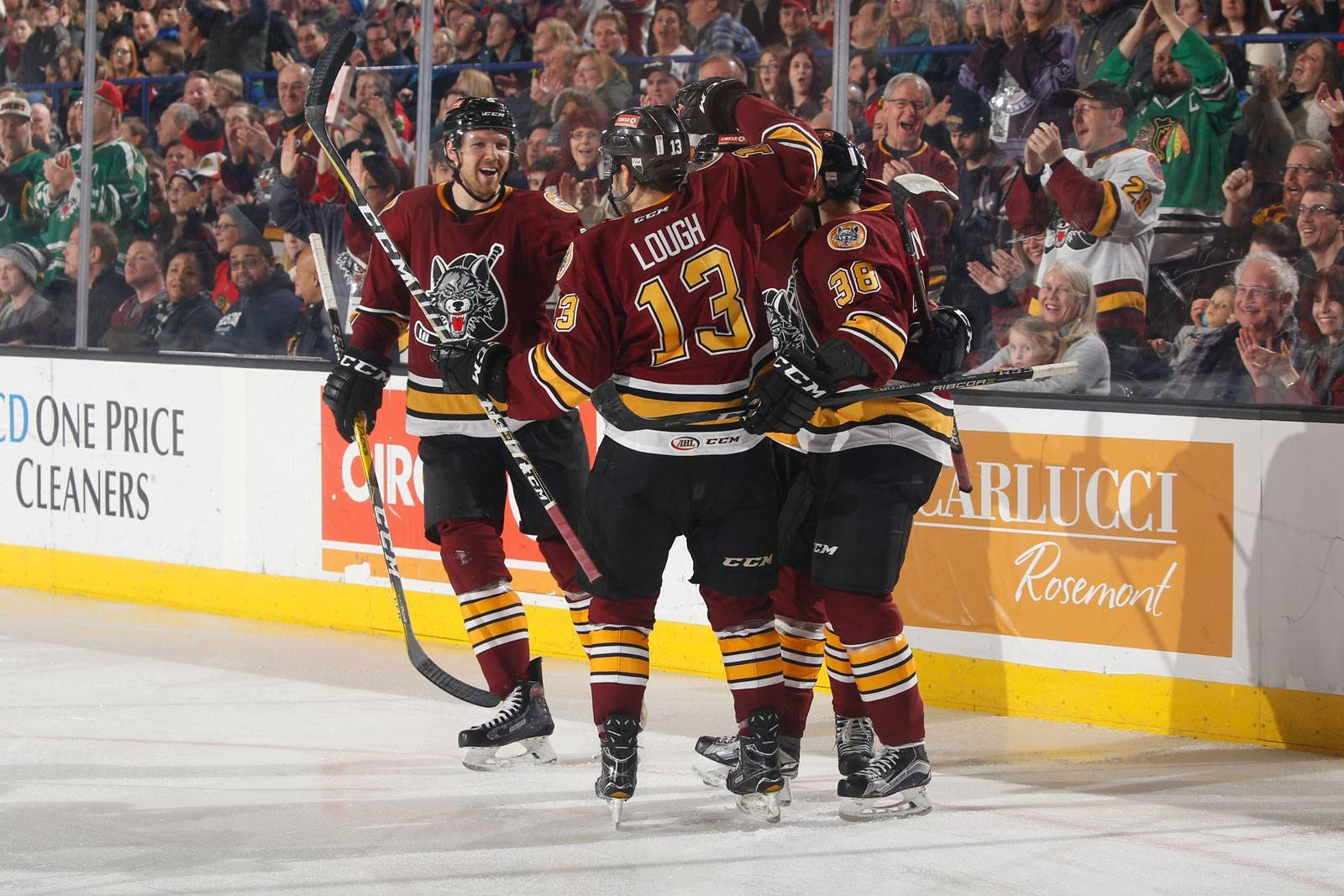 Defenseman Griffin Reinhart (from left), defenseman Kevin Lough and forward Tomas Hyka (38) celebrate another Chicago Wolves goal. The AHL team is riding a 14-game point streak.