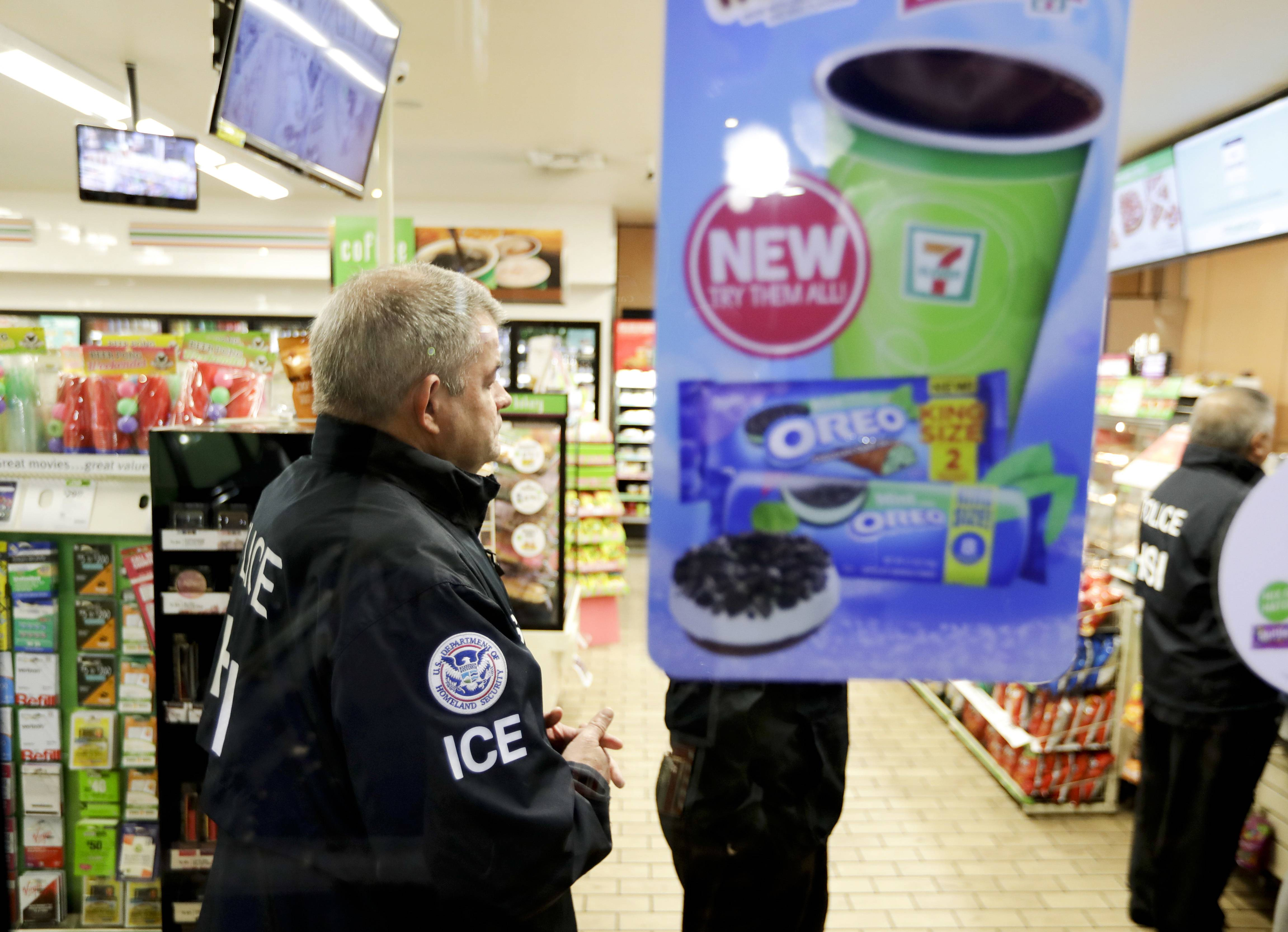 U.S. Immigration and Customs Enforcement agents serve an employment audit notice at a 7-Eleven convenience store Wednesday in Los Angeles. Agents said they targeted about 100 7-Eleven stores nationwide Wednesday to open employment audits and interview workers.