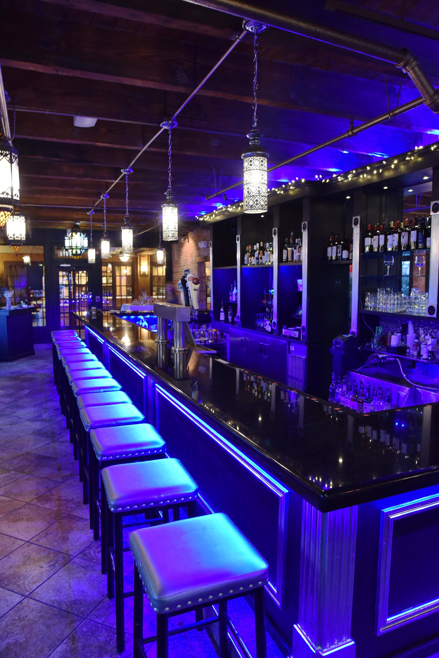 Blue accent lighting and gray leather bar stools exude a cool vibe at Eden on the River in St. Charles.