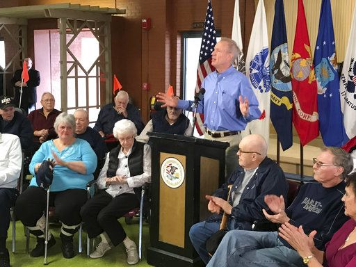 Flanked by residents of the Illinois Veterans Home, Gov. Bruce Rauner addresses members of the media during a news conference Wednesday, Jan. 10, 2018, at Smith Hall on the campus of the Illinois Veterans Home in Quincy, Ill. Rauner has been staying at the facility since last week to better understand the operations of the home after it experienced a Legionnaires' disease outbreak. (Phil Carlson/The Quincy Herald-Whig via AP)