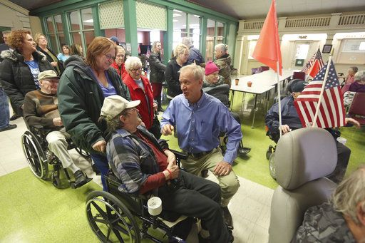 Gov. Bruce Rauner, kneeling at center, talks with members of the Illinois Veterans Home after a news conference Wednesday, Jan. 10, 2018, at Smith Hall on the campus of the Illinois Veterans Home in Quincy, Ill. Rauner has been staying at the facility since last week to better understand the operations of the home after it experienced a Legionnaires' disease outbreak. (Phil Carlson/The Quincy Herald-Whig via AP)