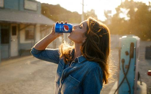 This photo released by Pepsi shows actress-model Cindy Crawford in a scene from her 2018 Pepsi commercial which will premiere during Super Bowl LII on Feb. 4. The new ad includes her son, Presley Walker Gerber, as well as footage from Michael Jackson's memorable Pepsi commercial. (Pepsi via AP)