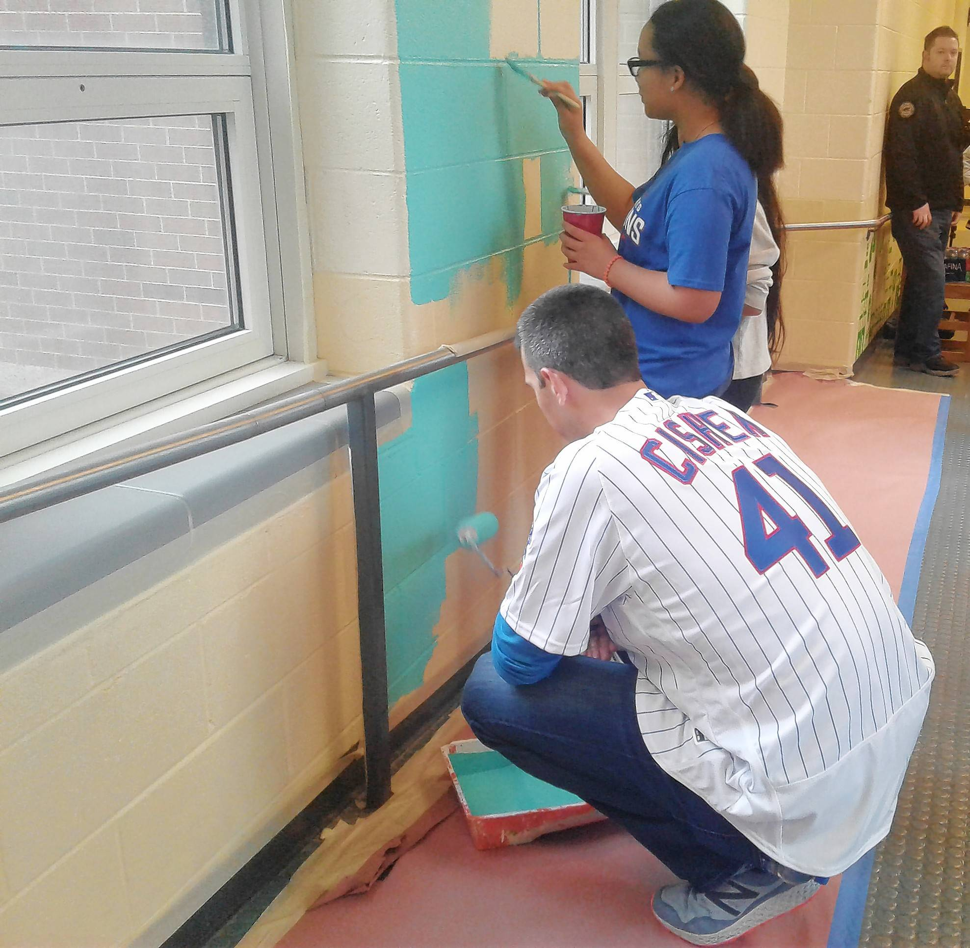 "Recently signed Cubs reliever Steve Cishek helps students paint a wall at Kilmer Elementary School in the Rogers Park neighborhood of Chicago. Other Cubs staff members were on hand as part of the team's ""service day"" program."