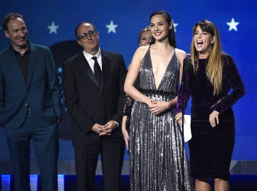 "Gal Gadot, center, Patty Jenkins and the crew of ""Wonder Woman"" accept the award for best action movie at the 23rd annual Critics' Choice Awards at the Barker Hangar on Thursday, Jan. 11, 2018, in Santa Monica, Calif. (Photo by Chris Pizzello/Invision/AP)"