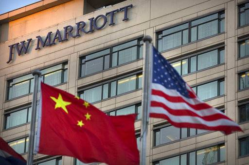 Chinese and American flags fly outside of a JW Marriott hotel in Beijing, Thursday, Jan. 11, 2018. The Marriot hotel chain apologized Thursday to China's government for referring to Tibet and self-ruled Taiwan as countries in a customer survey that news reports said Chinese police investigated as a possible crime.