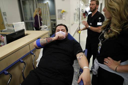 In this Jan. 10, 2017 image, Donnie Cardenas recovers from the flu at the Palomar Medical Center in Escondido, Calif., on Wednesday, Jan. 10, 2018. The San Diego County resident said he was battling a heavy cough for days before a spike his temperature sent him into the emergency room.