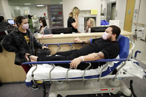 Donnie Cardenas, right, waits in an emergency room hallway alongside roommate Torrey Jewett, left, as he recovers from the flu at the Palomar Medical Center in Escondido, Calif., on Wednesday, Jan. 10, 2018. The San Diego County resident said he was battling a heavy cough for days before a spike his temperature sent him into the emergency room.