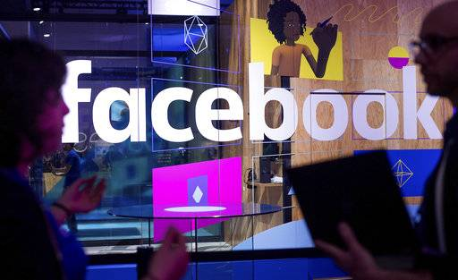 "FILE - In this April 18, 2017, file photo, conference workers speak in front of a demo booth at Facebook's annual F8 developer conference in San Jose, Calif. Facebook said Thursday, Jan. 11, 2018, that it is tweaking what people see to make their time on it more ""meaningful.� The changes come as Facebook faces criticism that social media can make people feel depressed and isolated."