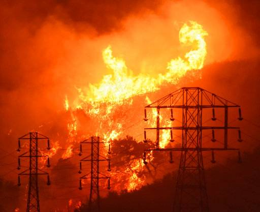 FILE - In this Saturday, Dec. 16, 2017, file photo provided by the Santa Barbara County Fire Department, flames burn near power lines in Sycamore Canyon near West Mountain Drive in Montecito, Calif. The largest wildfire on record in California, the Thomas fire, was declared contained on Friday, Jan. 12, 2018, days after mud on the coastal mountain slopes it scorched crashed down on homes during a storm, killing at least 18 people. (Mike Eliason/Santa Barbara County Fire Department via AP, File)