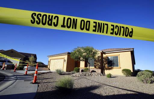 FILE - This Oct. 2, 2017 file photo shows police tape blocking off the home of Stephen Craig Paddock in Mesquite, Nev. A federal judge is being asked to unseal documents telling what federal agents learned before searching properties belonging to the gunman responsible for the Oct. 1, 2017 massacre on the Las Vegas Strip. Prosecutors aren't opposing a Friday, Jan. 12, 2018 request from media organizations for U.S. District Judge Jennifer Dorsey to release redacted affidavits underlying warrants for locations including Stephen Paddock's home in Mesquite.