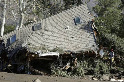 Emergency crew members search an area near houses damaged by storms in Montecito, Calif., Friday, Jan. 12, 2018. The number of missing after a California mudslide has fluctuated wildly, due to shifting definitions, the inherent uncertainty that follows a natural disaster, and just plain human error.