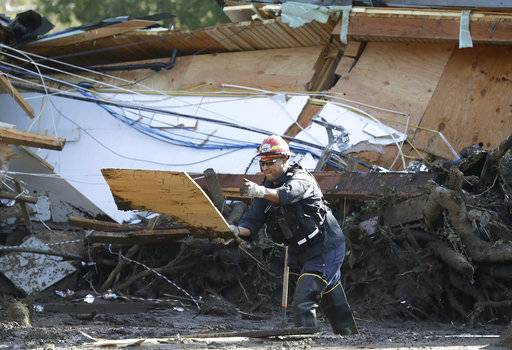 Emergency crew members search an area damaged by storms in Montecito, Calif., Friday, Jan. 12, 2018. The number of missing after a California mudslide has fluctuated wildly, due to shifting definitions, the inherent uncertainty that follows a natural disaster, and just plain human error.