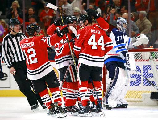 Chicago Blackhawks defenseman Jan Rutta (44) celebrates with teammates after his goal as Winnipeg Jets goaltender Connor Hellebuyck (37) stands in the net during the second period of an NHL hockey game Friday, Jan. 12, 2018, in Chicago.