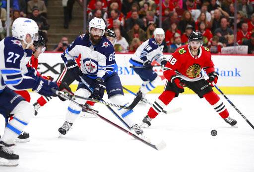 Winnipeg Jets center Mathieu Perreault (85) makes a pass to left wing Nikolaj Ehlers (27) as Chicago Blackhawks left wing Vinnie Hinostroza (48) watches during the first period of an NHL hockey game Friday, Jan. 12, 2018, in Chicago.