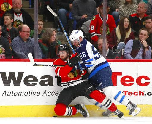 Winnipeg Jets center Marko Dano (56) checks Chicago Blackhawks left wing Vinnie Hinostroza (48) into the boards during the first period of an NHL hockey game Friday, Jan. 12, 2018, in Chicago.