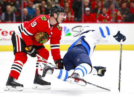 Chicago Blackhawks center Jonathan Toews (19) trips Winnipeg Jets center Marko Dano during the first period of an NHL hockey game Friday, Jan. 12, 2018, in Chicago.