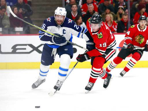 Winnipeg Jets right wing Blake Wheeler (26) and Chicago Blackhawks center Jonathan Toews (19) vie for the puck during the first period of an NHL hockey game Friday, Jan. 12, 2018, in Chicago.