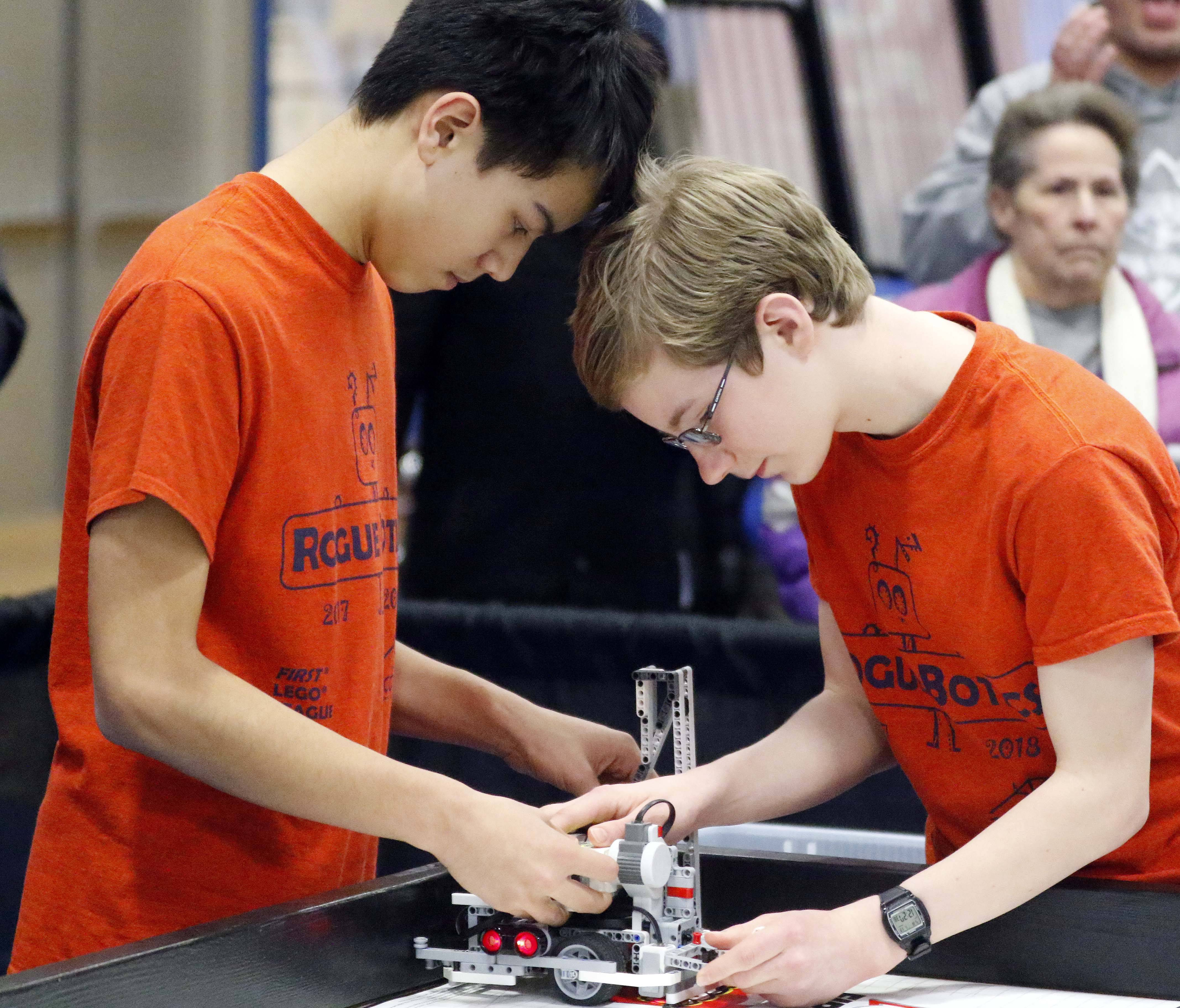 Sean Liu, left, and Logan Cunz, both 14, from Kaneland Harter Middle School in Sugar Grove, change out part of their Lego robot Saturday during the First Lego Championship Tournament at Elgin Community College where 50 teams from across the state competed.
