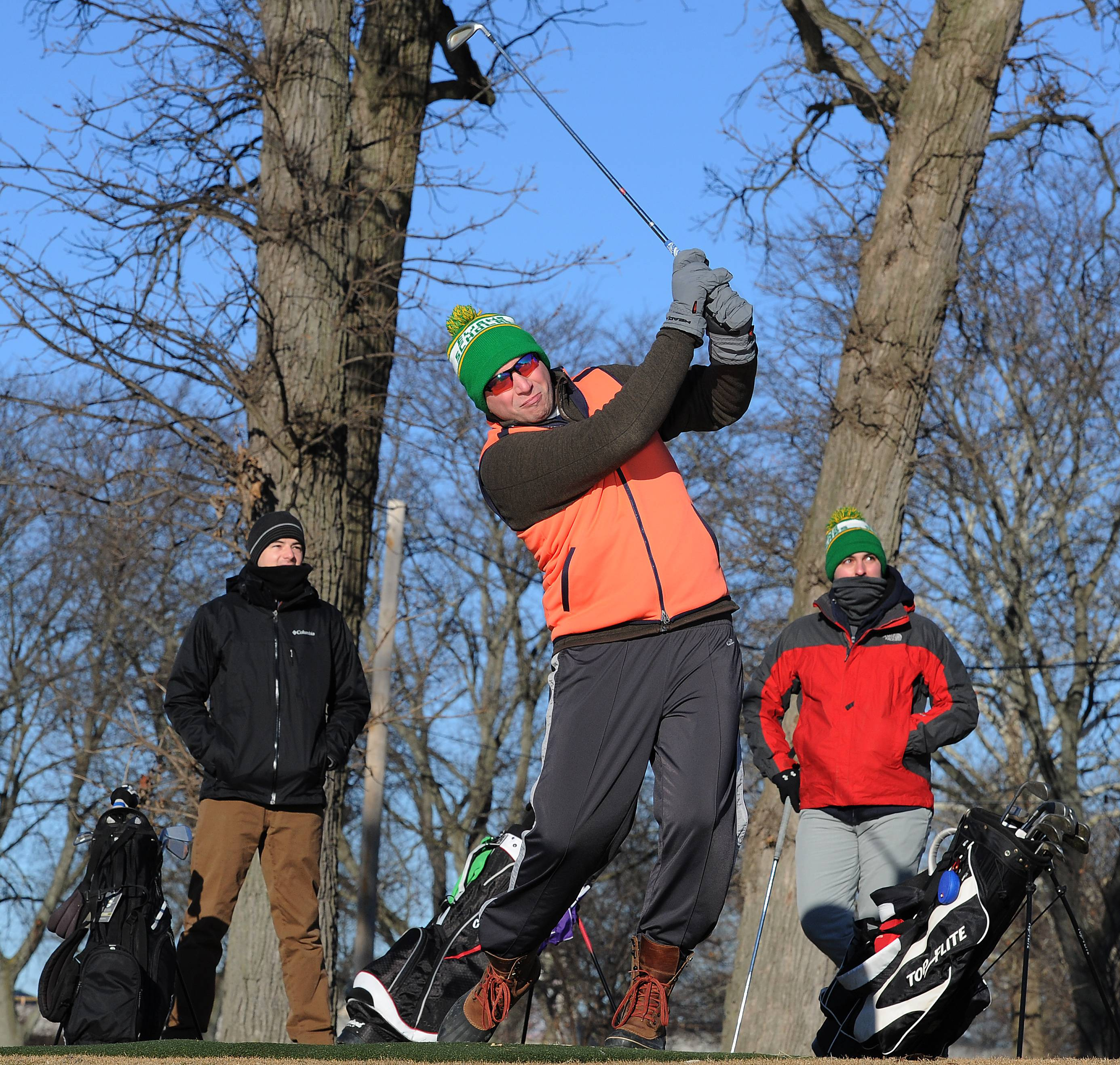 Des Plaines Mayor Matt Bogusz fires off the first shot at the Chili Open event in the brisk 12 degree temperature and January sunshine at the Golf Center in Des Plaines on Saturday.