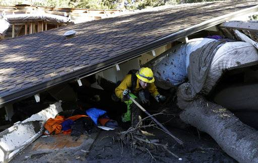 Colette Layton, bottom, of the Atascadero Fire Dept, searches a home Saturday, Jan. 13, 2018, in Montecito, Calif.  Most of the people of Montecito, a town usually known for its serenity and luxury, were under orders to stay out of town as gas and power were expected to be shut off Saturday for repairs.