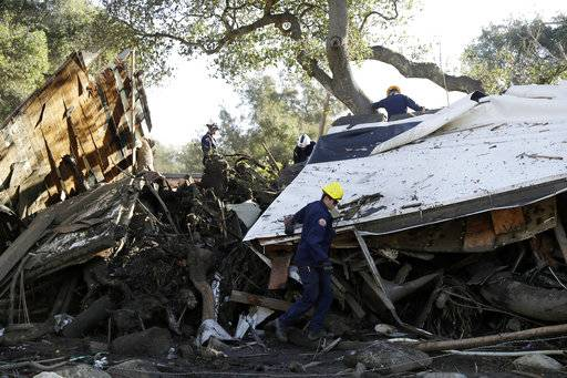 Search and rescue personnel scan a home in the aftermath of a mudslide Saturday, Jan. 13, 2018, in Montecito, Calif.  Most of the people of Montecito, a town usually known for its serenity and luxury, were under orders to stay out of town as gas and power were expected to be shut off Saturday for repairs.