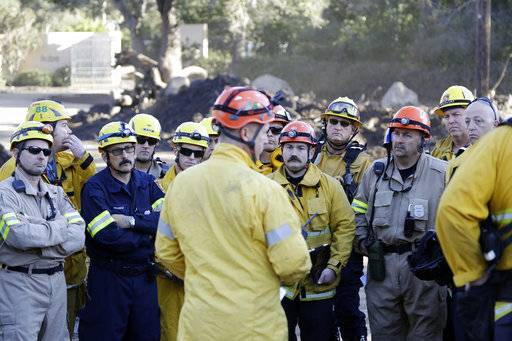 Search and rescue crews hold a meeting along Hot Springs Rd. in the aftermath of a mudslide Saturday, Jan. 13, 2018, in Montecito, Calif.