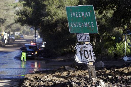 A mud-covered sign over the closed Highway 101 is seen at an overpass Saturday, Jan. 13, 2018, in Montecito, Calif.  Most of the people of Montecito, a town usually known for its serenity and luxury, were under orders to stay out of town as gas and power were expected to be shut off Saturday for repairs.