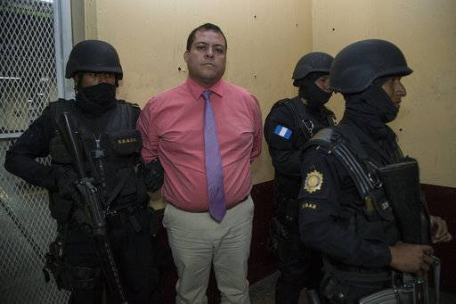 Ruling-party lawmaker Julio Juarez Ramirez is escorted by police to a courtroom in Guatemala City, Saturday, Jan. 13, 2018. Authorities in Guatemala arrested Juarez Ramirez accused of orchestrating the murder of two journalists in 2015. (AP Photo/Moises Castillo)