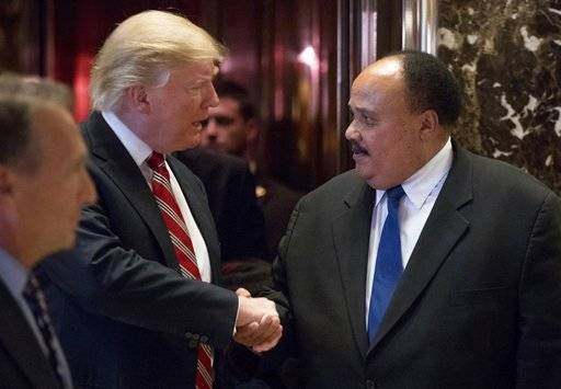 "FILE- In this Jan. 16, 2017 file photo, President-elect Donald Trump shakes hands with Martin Luther King III, son of Martin Luther King Jr. at Trump Tower in New York. King III, met with Trump on the last King holiday, four days before Trump took office. He spoke to the then-president-elect about the importance of voting rights - only to see Trump establish a now-defunct commission to investigate voter fraud, which some saw as a move to intimidate minority voters. ""I would like to believe that the president's intentions are not to be divisive, but much of what he says seems or feels to be divisive,"" King III told AP in an interview. ""It would be wonderful to have a president who talked about bringing America together and exhibited that, who was involved in doing a social project ... that would show humility."""