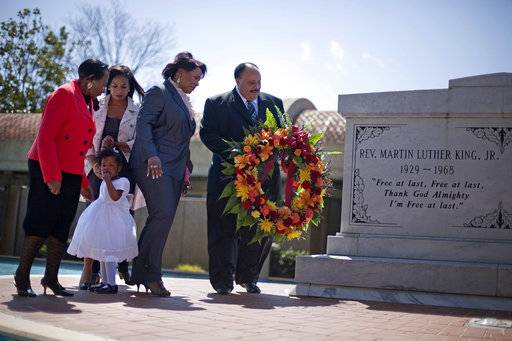 FILE- In this April 4, 2011 file photo, Martin Luther King III, right, the son of Rev. Martin Luther King Jr., lays a wreath at the crypt of his father along with from right, Rev. King's daughter, Rev. Bernice King, granddaughter Yolanda, 2, her mother Arndrea King, and Christine King Farris, sister of Dr. King Jr., on the 43rd anniversary of his assassination in Atlanta. The first Martin Luther King Jr. holiday of Donald Trump's presidency is taking place amid a racial firestorm of Trump's own making.