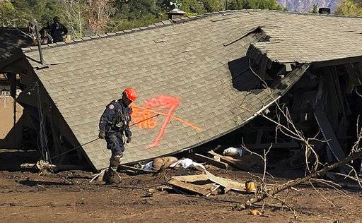 This photo provided by the Santa Barbara County Fire Department shows firefighters making secondary searches on homes damaged and destroyed by deadly rain and mudflow in Montecito, Calif., Friday, Jan. 12, 2018. Dozens of homes were swept away or heavily damaged and several people were killed Tuesday, Jan. 9, as downpours sent mud and boulders roaring down hills stripped of vegetation by a the gigantic Thomas wildfire that raged in Southern California last month. (Mike Eliason/Santa Barbara County Fire Department via AP)