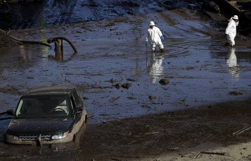 A work crew cleans up an area of Highway 101 that flooded in Montecito, Calif., Friday, Jan. 12, 2018. The number of missing after a California mudslide has fluctuated wildly, due to shifting definitions, the inherent uncertainty that follows a natural disaster, and just plain human error.