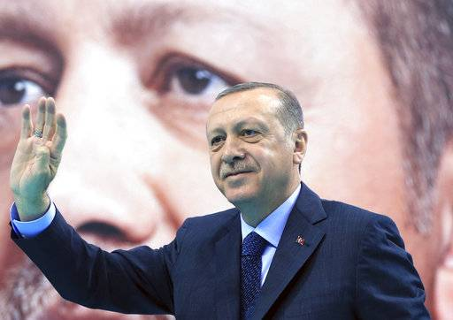 Turkey's President Recep Tayyip Erdogan waves to supporters of his ruling Justice and Development Party (AKP), at a rally in Elazig, eastern Turkey, Saturday, Jan. 13, 2018. Erdogan has said Turkey will oust Kurdish militants from Afrin, northern Syria, as the military shelled the area from across the border. Turkey considers the YPG a terror group and an extension of the Kurdish insurgency within its own borders. (Pool Photo via AP)
