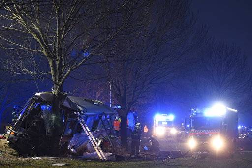 Rescuers work at a bus after its collision with a car at Horomerice near Prague, Czech Republic, Friday Jan. 12, 2018. The accident claimed three lives and 30 injuries. At least ten people have serious injuries. (Ondrej Deml/CTK via AP)