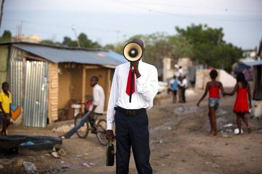 In this Sunday, Jan. 7, 2018 photo, a bullhorn preacher evangelizes to the passing residents of the Caradeux refugee camp set up nearly eight years ago for people displaced by the 2010 earthquake, in Port-au-Prince, Haiti. Just before 5 p.m. on Jan. 12, 2010 a magnitude 7.0 earthquake upended life in Port-au-Prince, Haiti, killing more than 300,000 people by some estimates and destroying hundreds of thousands of homes. For many of those left homeless, life hasn't yet returned to normal. (AP Photo/Dieu Nalio Chery)